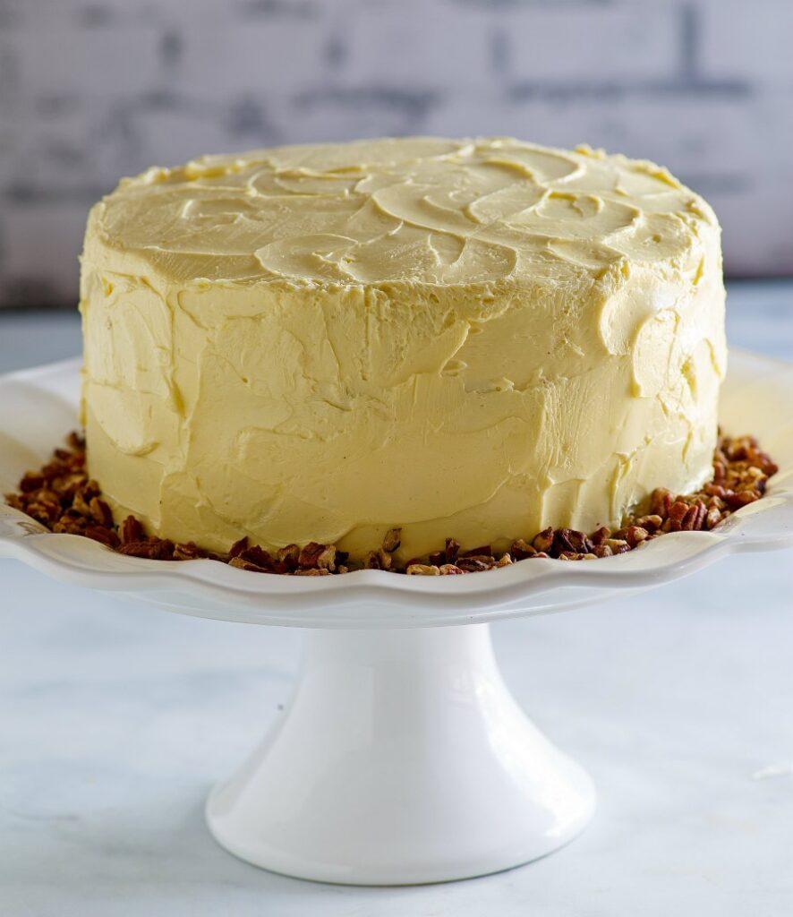 round maple cake on white pedestal.