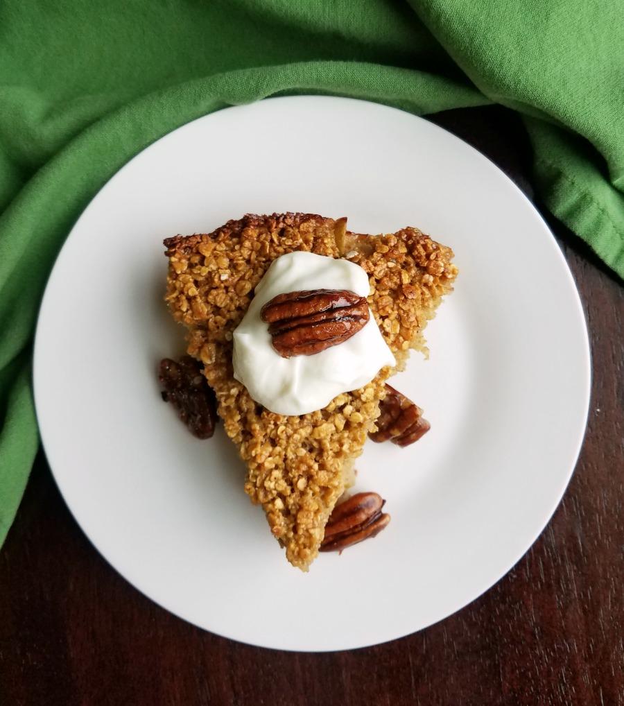 shiny pecans and yogurt on slice of apple pie baked oatmeal.