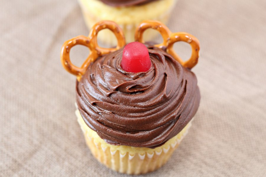 cupcake with chocolate frosting, red candy nose and pretzel twist antlers.