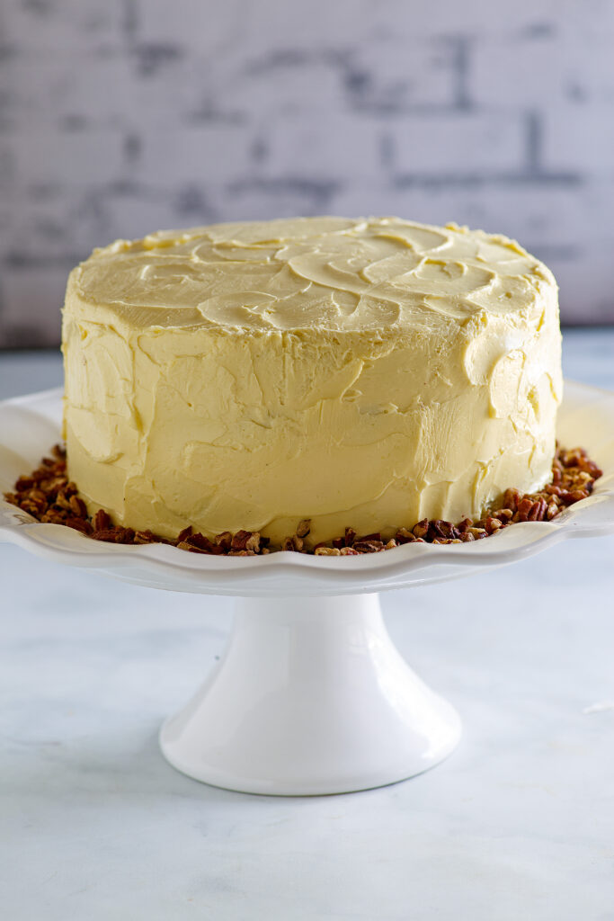 maple frosted layer cake with pecans on white cake stand