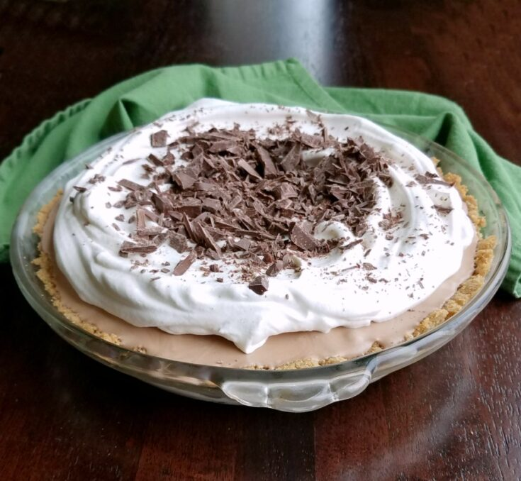 Frozen mint meltaway pie topped with whipped cream and chopped Frango mints, ready to be served.