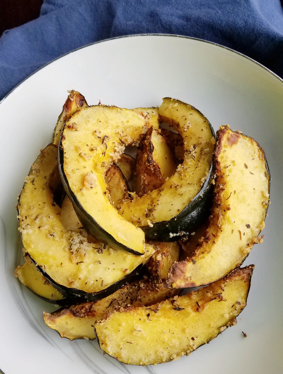 close up of roasted acorn squash slices coated in Parmesan and herbs