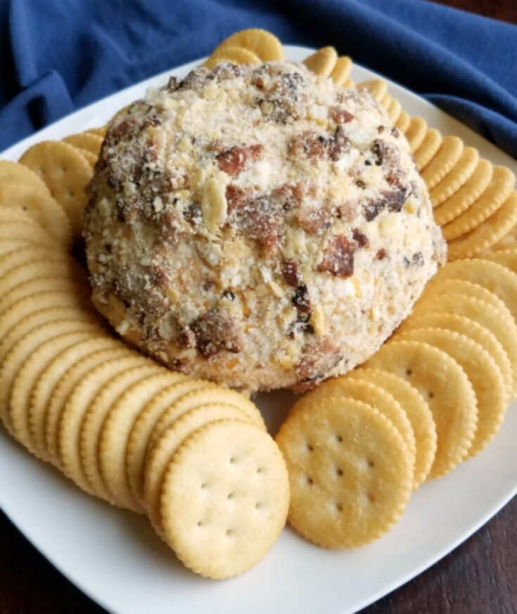 cheddar bacon ranch cheese ball on plate with crackers.