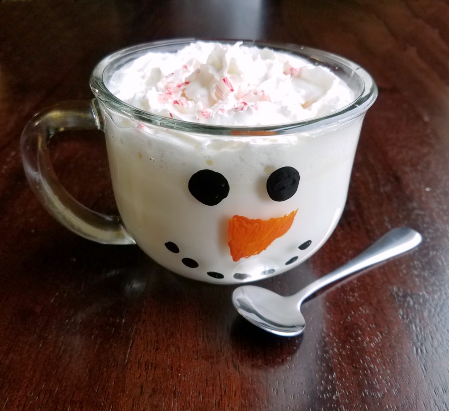 glass snowman mug filled with white hot chocolate.