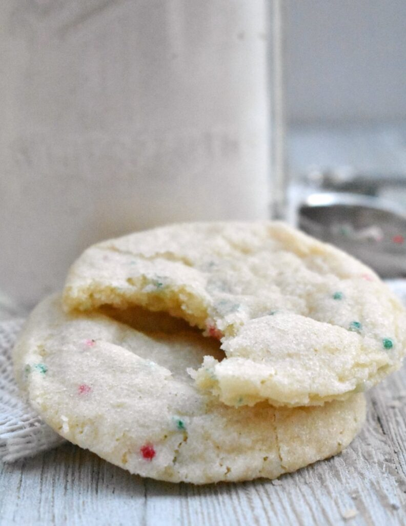 couple of sprinkle sugar cookies one with a bite taken out.