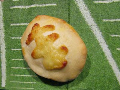 small stuffed pizza in shape of football on football field napkin