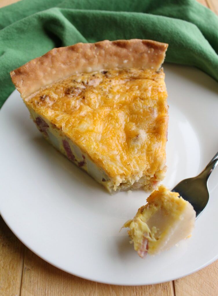 Slice of ham, potato and cheese quiche with first bite on fork.