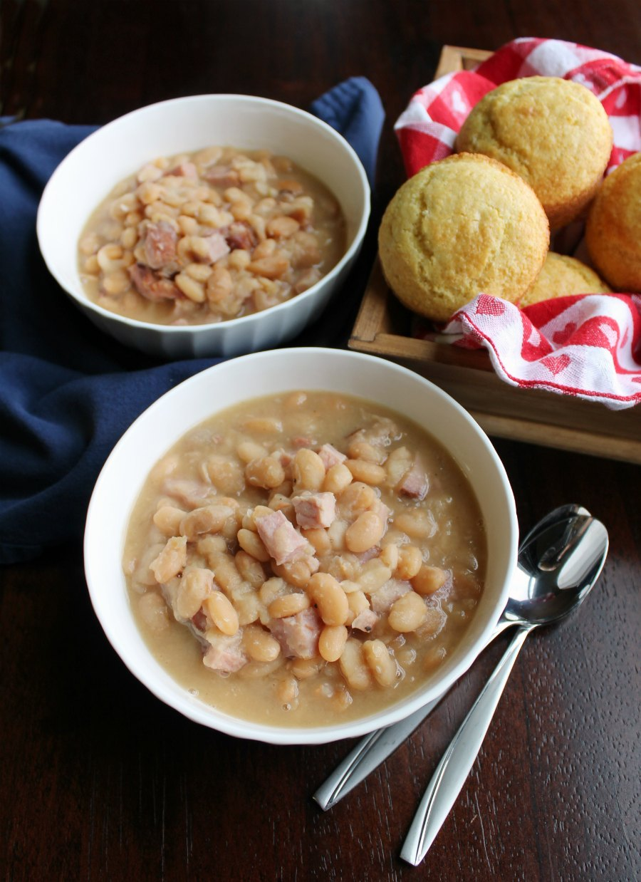 bowls of ham and beans next to basket of corn muffin