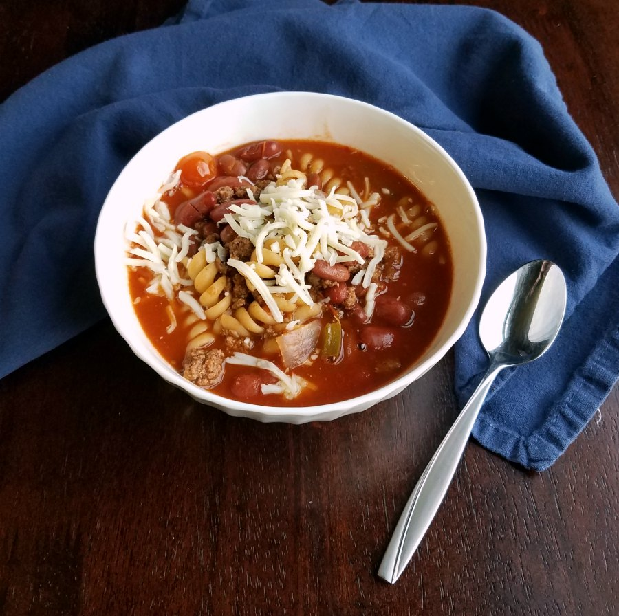 bowl of chili mac soup with cheese on top, ready to eat.