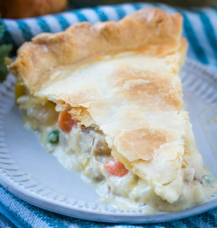 slice of creamy chicken pot pie with vegetable and potato filling served on plate