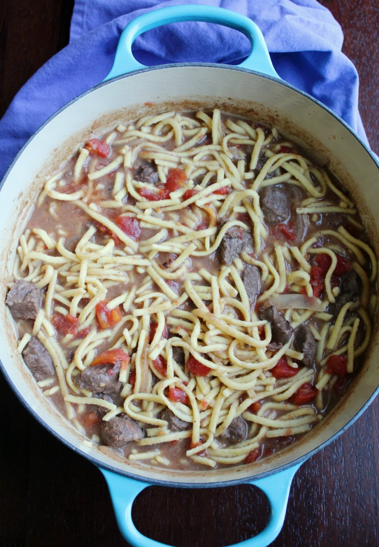 beef and noodles with tomatoes in dutch oven.