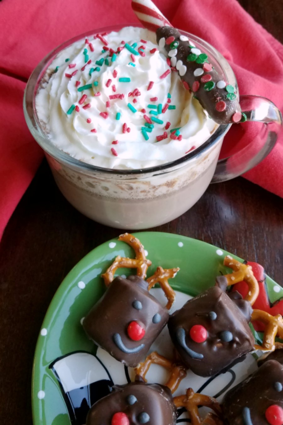 plate of chocolate dipped marshmallows next to mug of hot chocolate