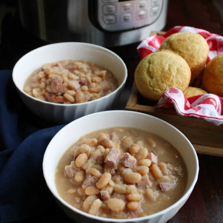 Bowls of creamy ham and bean soup with basket of corn muffins in front of instant pot.