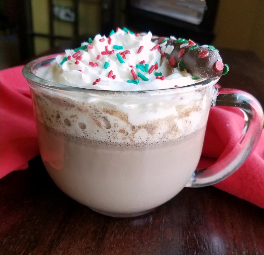 glass mug of creamy hot cocoa topped with whipped cream, sprinkles and a chocolate dipped peppermint stick