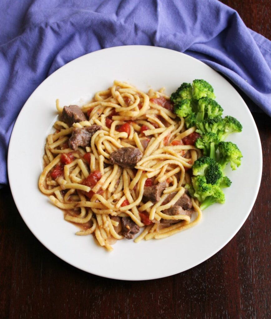 plateful of egg noodles cooked in beef and tomato mixture served with broccoli.