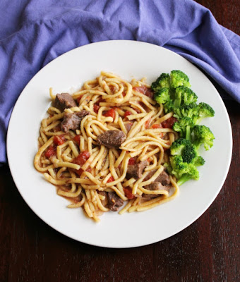 plateful of egg noodles cooked in beef and tomato mixture served with broccoli