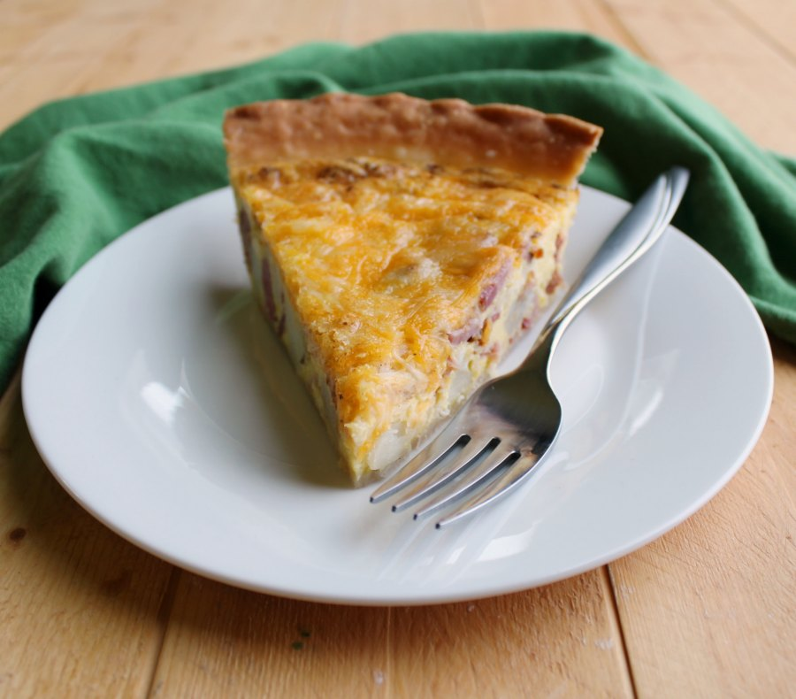 slice of ham potato and cheese quiche with fork,