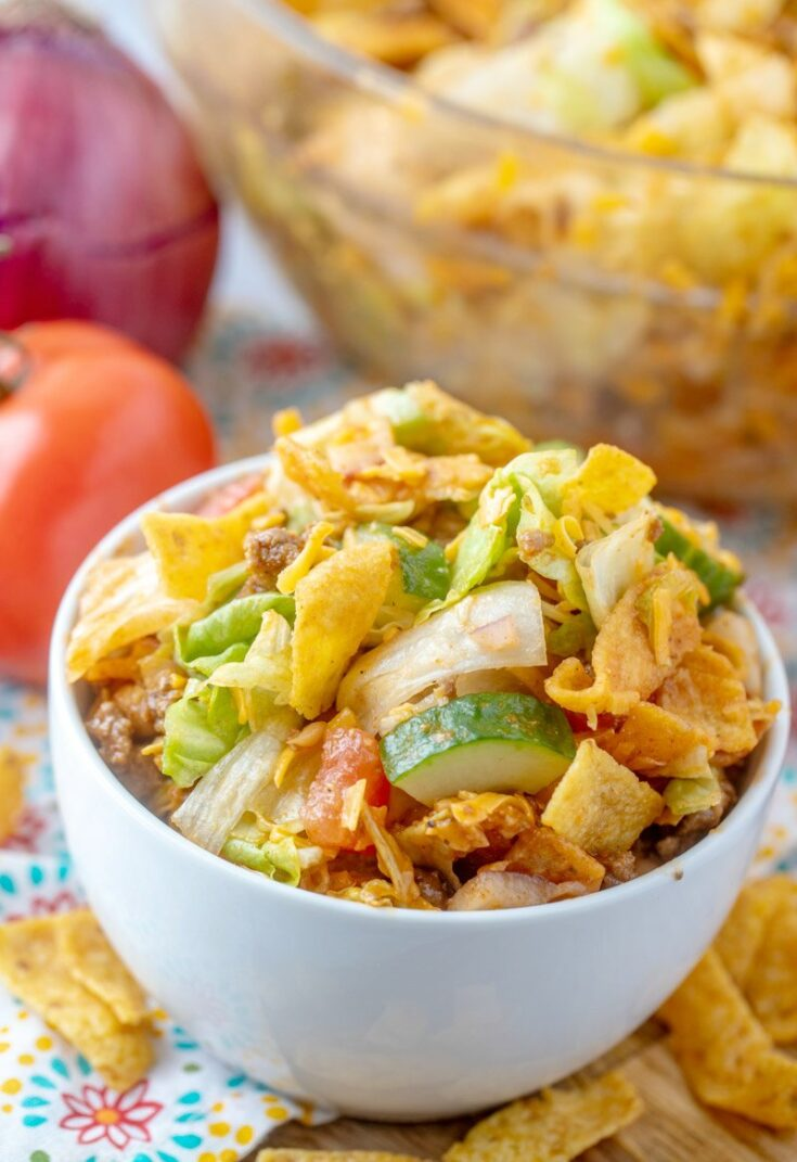 small bowl of frito taco salad in front of large serving bowl of salad.