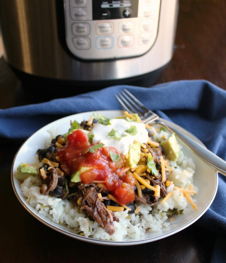 burrito bowl made of rice topped with salsa chicken, salsa, sour cream, cheese etc. in front of instant pot