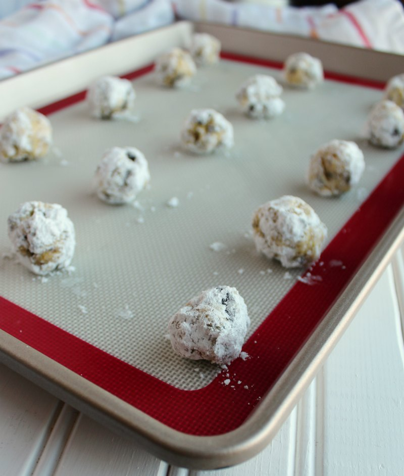 balls of cookie dough rolled in powdered sugar on tray ready to bake.