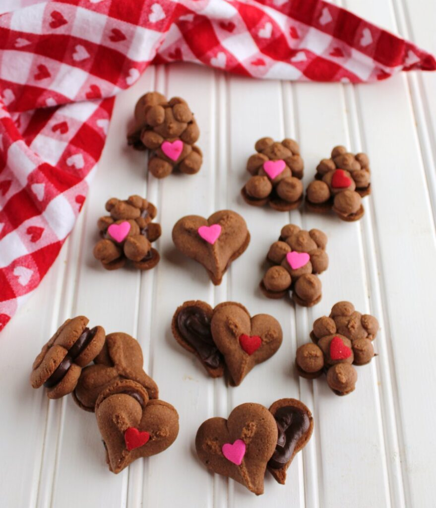 chocolate spritz cookies with chocolate ganache between them for Valentine's Day.