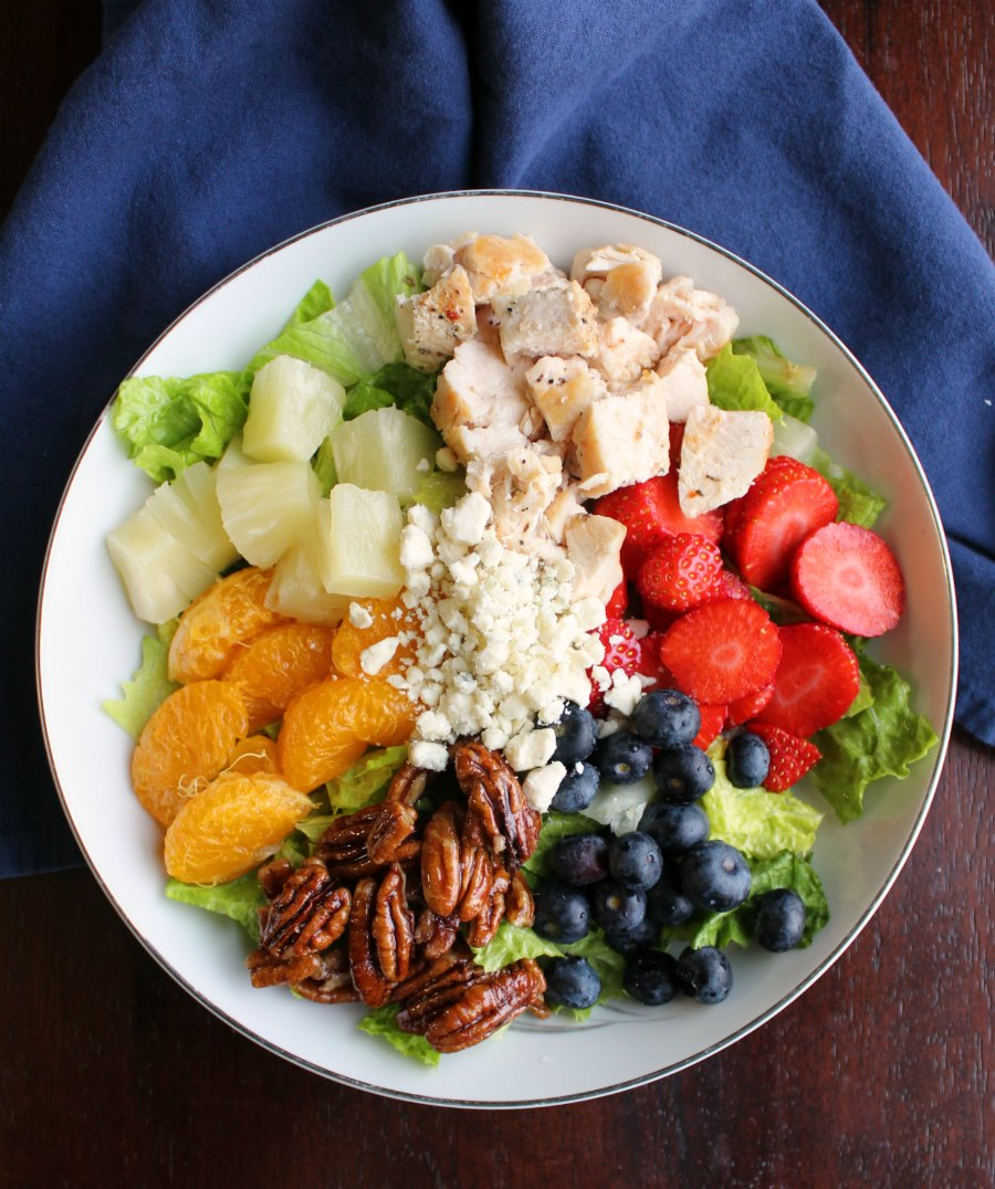 bowl of salad topped with chicken, fruit, cheese and pecans
