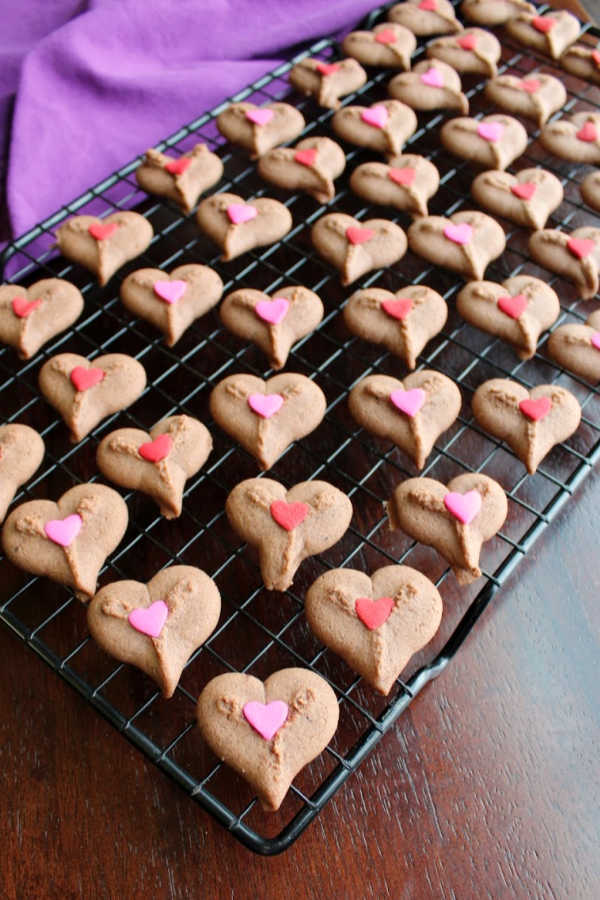 cooling rack full of chocolate spritz heart cookies with heart sprinkles.
