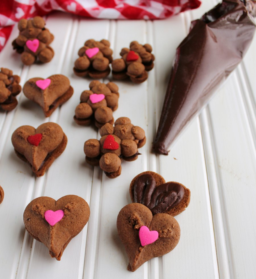 chocolate teddy bear and heart cookies being filled with piping bag full of dark chocolate ganache frosting.