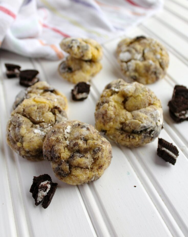 soft powdered sugar coated cookies with oreos baked inside with additional oreo pieces scattered about.