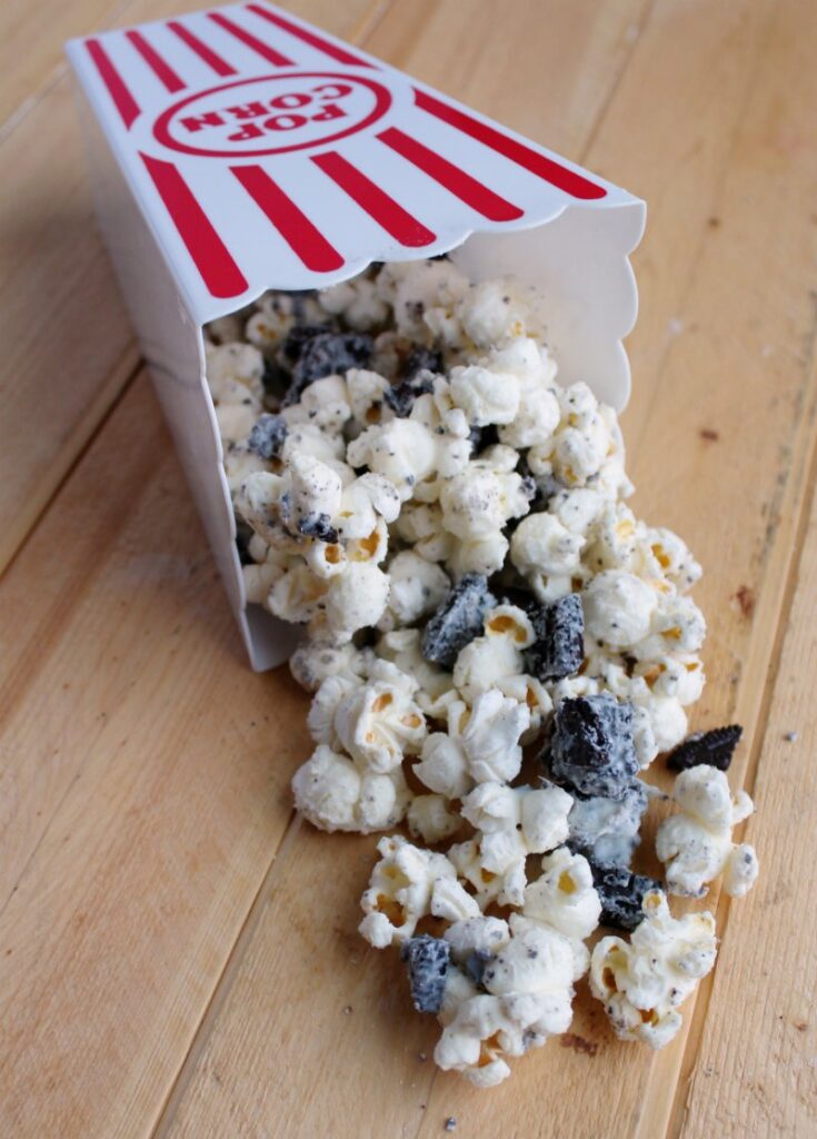 tub of popcorn coated in white chocolate with bits of oreos in it tipped over and spilling out