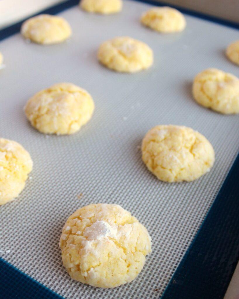 tray of freshly baked powdered sugar coated lemon cookies.