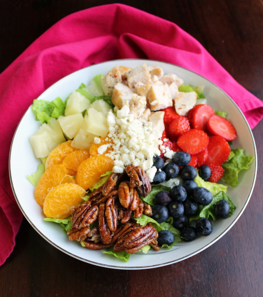 big bowl of salad greens topped with pineapple, orange sections, berries, chicken, pecans and cheese.