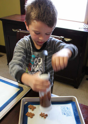 little dude using cookie press to form bear and heart shaped chocolate cookies