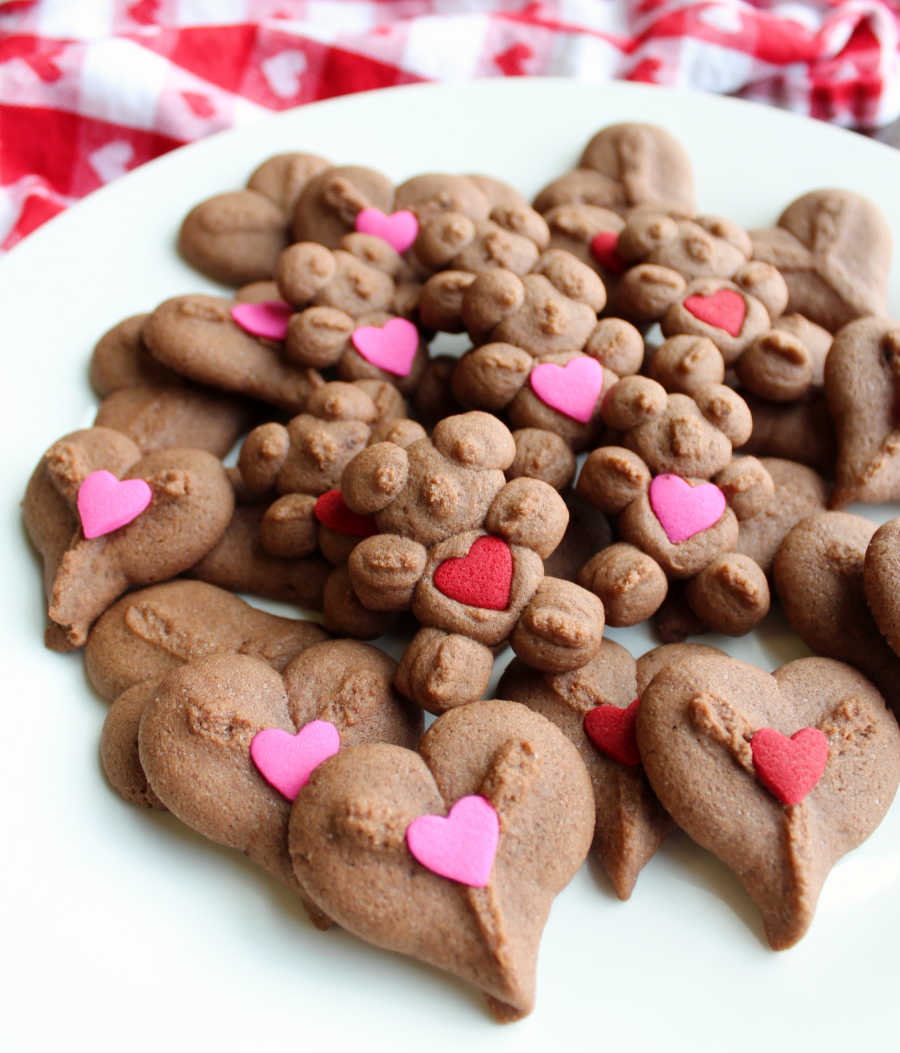 chocolate spritz cookies in the shape of bears and hearts with heart sprinkles
