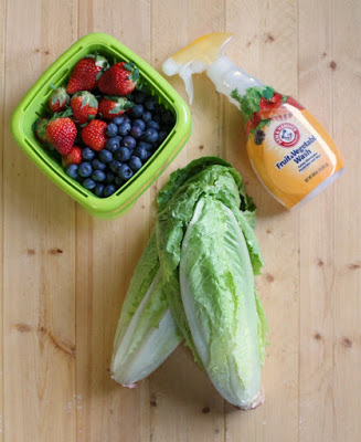 heads of romaine lettuce next to a berry box filled with blueberries and strawberries with a spray bottle of arm & hammer fruit and vegetable wash