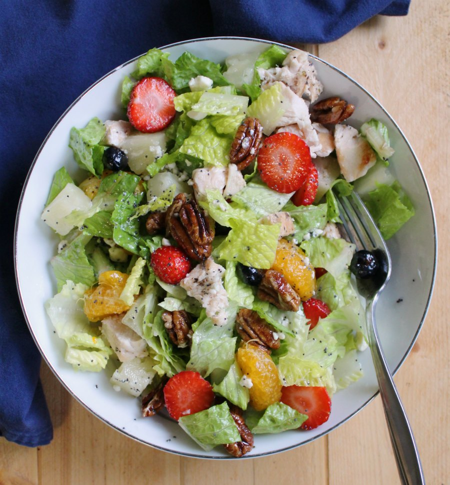 bowl of salad with romaine tossed with berries, oranges, pineapple, pecans, chicken and cheese.