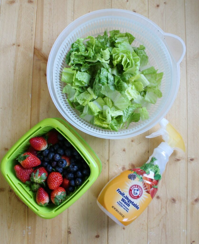 lettuce in a salad spinner and berries in a berry box getting washed with arm & hammer fruit & vegetable wash.