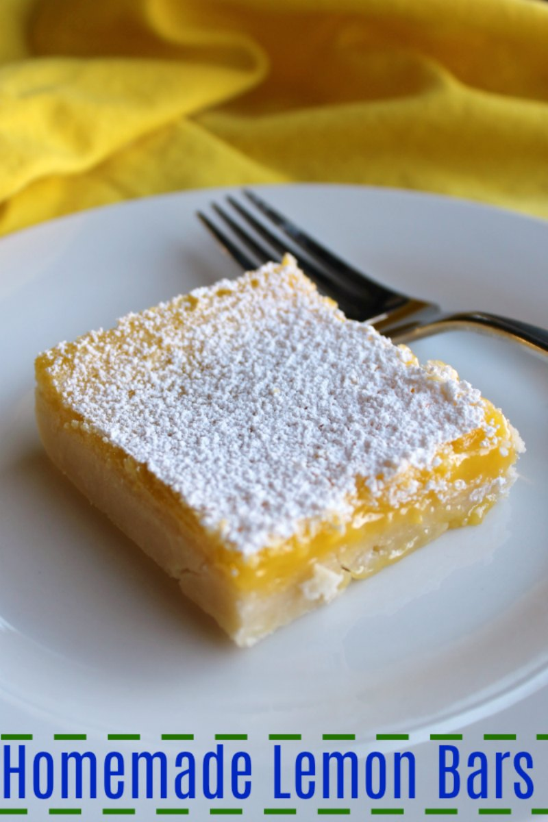 close up of lemon bar with shortbread crust and powdered sugar dusted on top.
