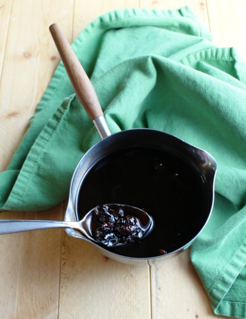 cherry syrup in saucepan ready to be spooned over crepes.