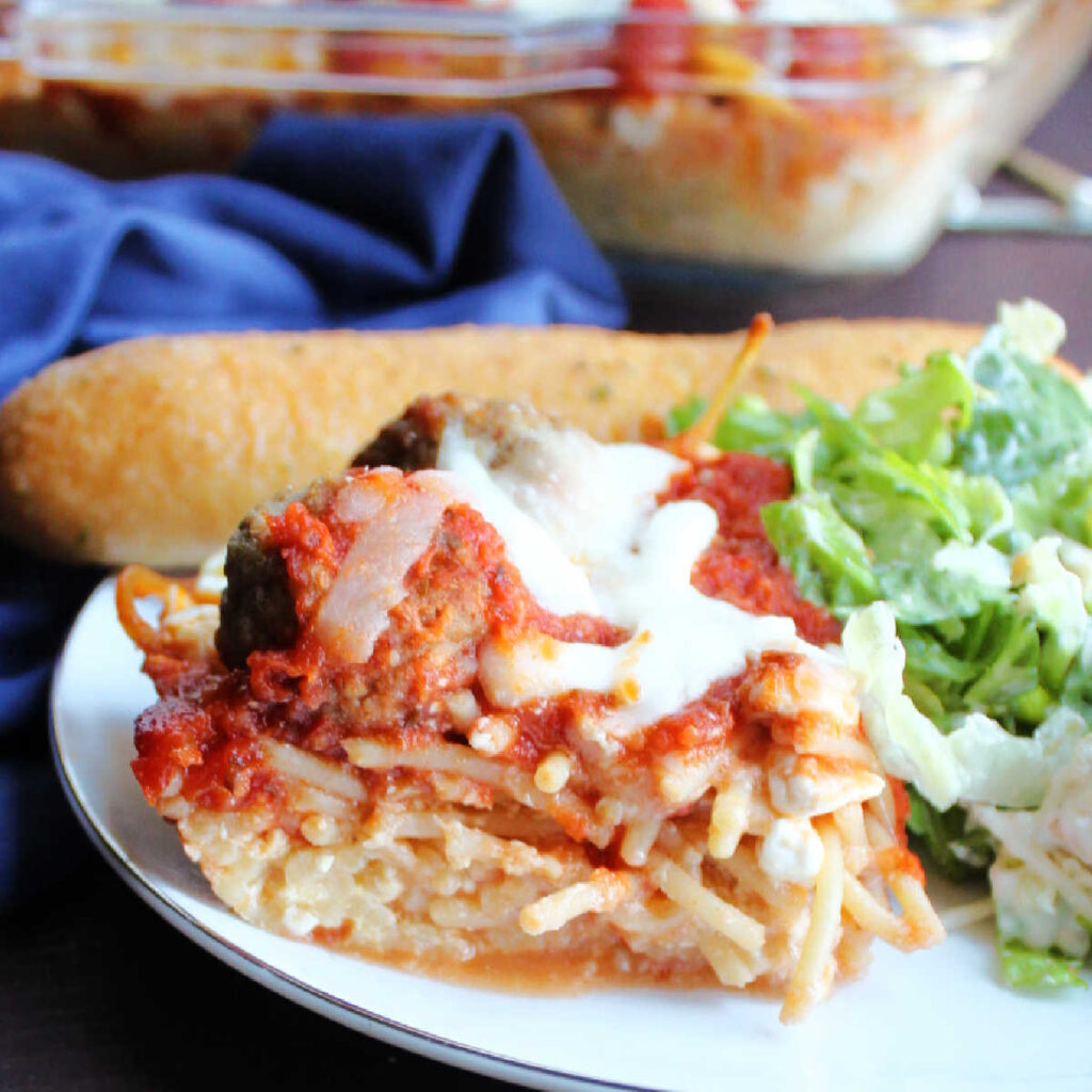 close up piece of spaghetti casserole with cheesy pasta layer topped with meatballs, tomato sauce and more cheese.