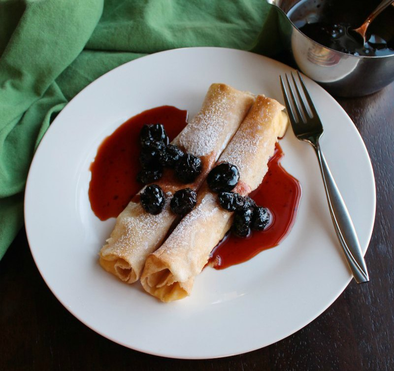 close up of plate of lemon ricotta stuffed crepes with cherry syrup