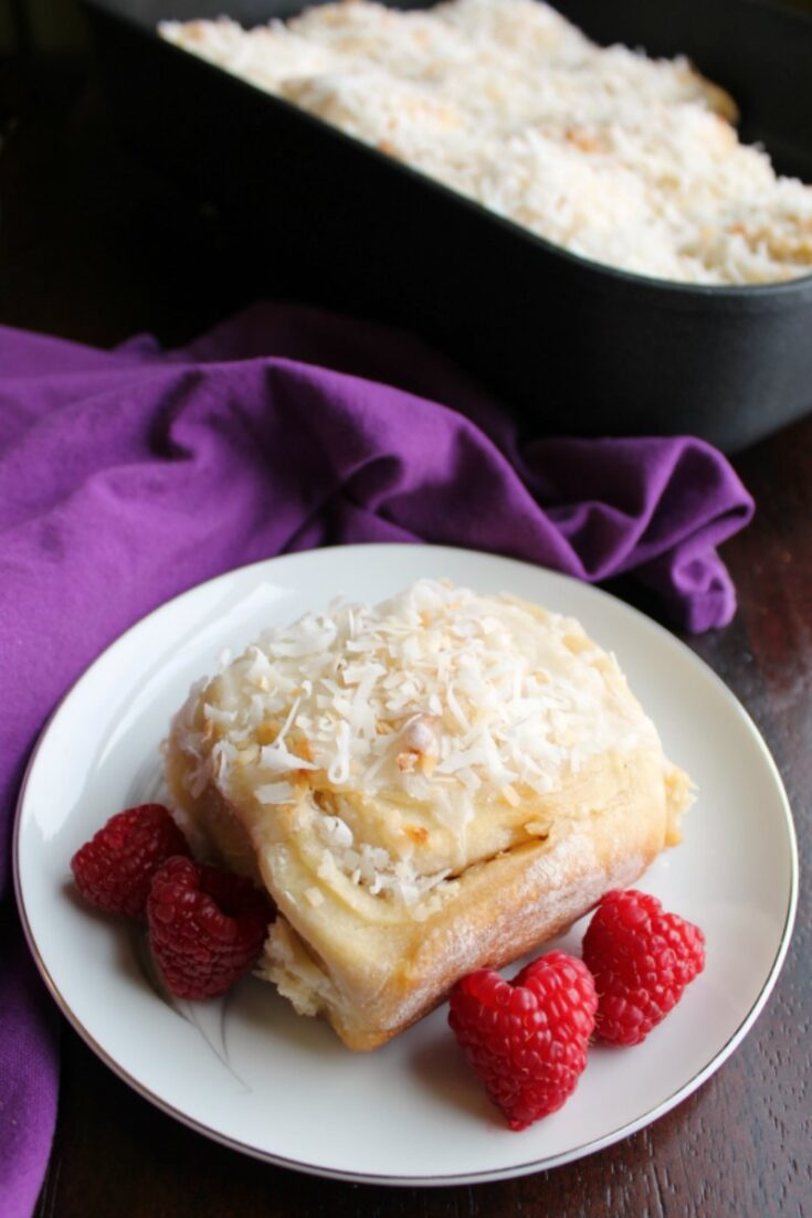 coconut sweet roll served with raspberries in front of pan of rolls
