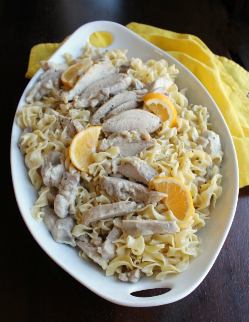 large serving dish filled with pasta, creamy lemon chicken and chicken wedges.