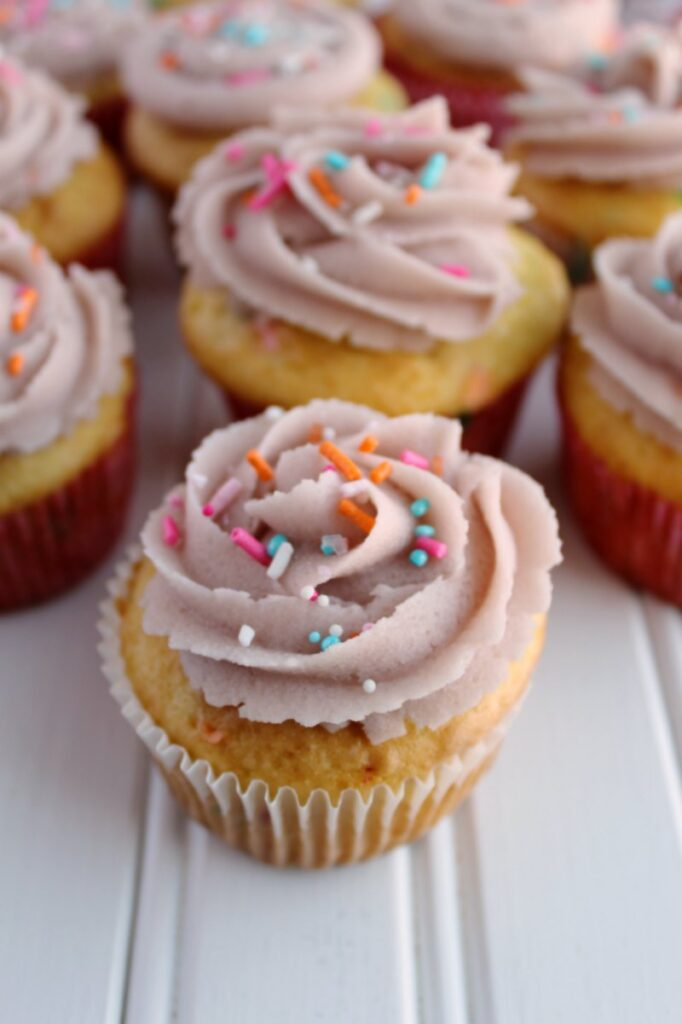 cupcakes decorated with sugar cookie dough frosting and cute sprinkles.