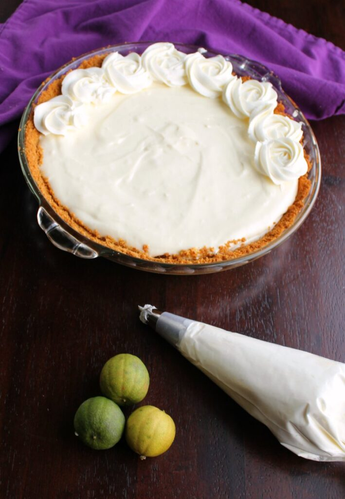 piping cream cheese whipped cream rosettes on top of key lime pie.