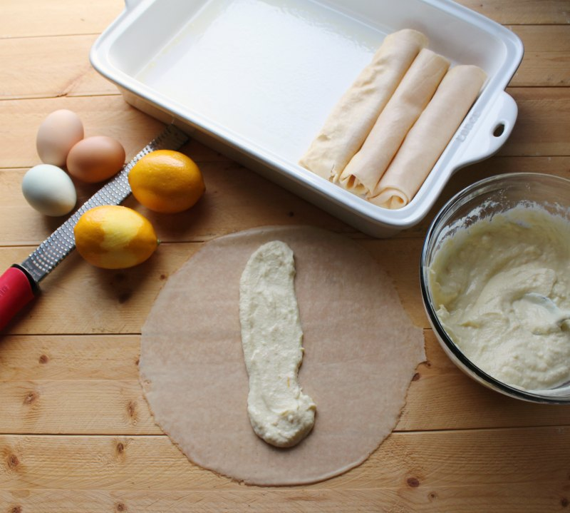 crepe being filled with lemon ricotta filling with zested lemon and eggs nearby.