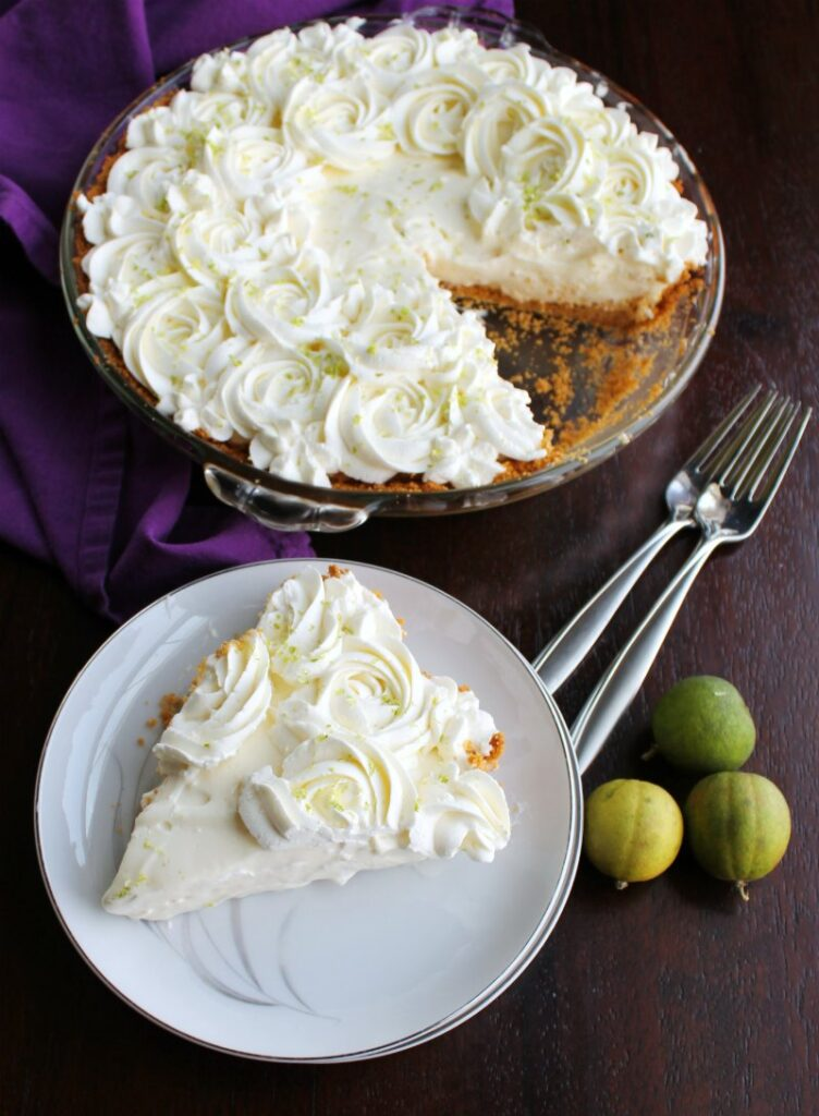 slice of key lime pie on plate with key limes and remaining pie in background