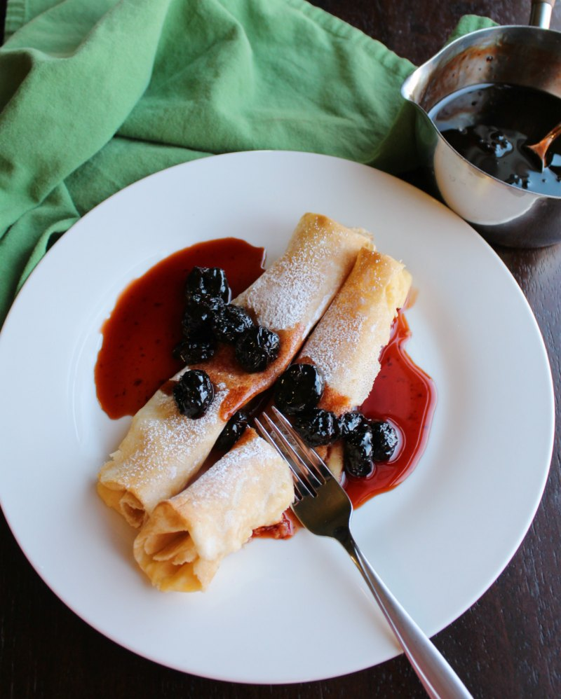 fork cutting into stuffed crepe covered with cherry syrup. pan of syrup in background.