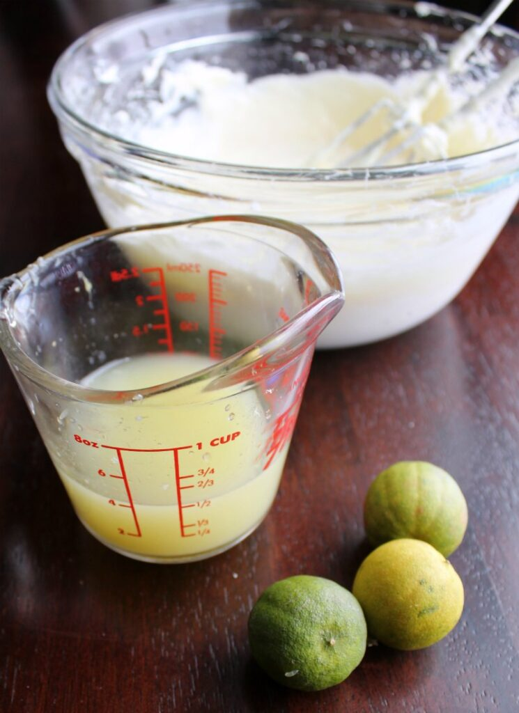 key limes next to measuring cup of key lime juice with bowl of whipped cream cheese in background.