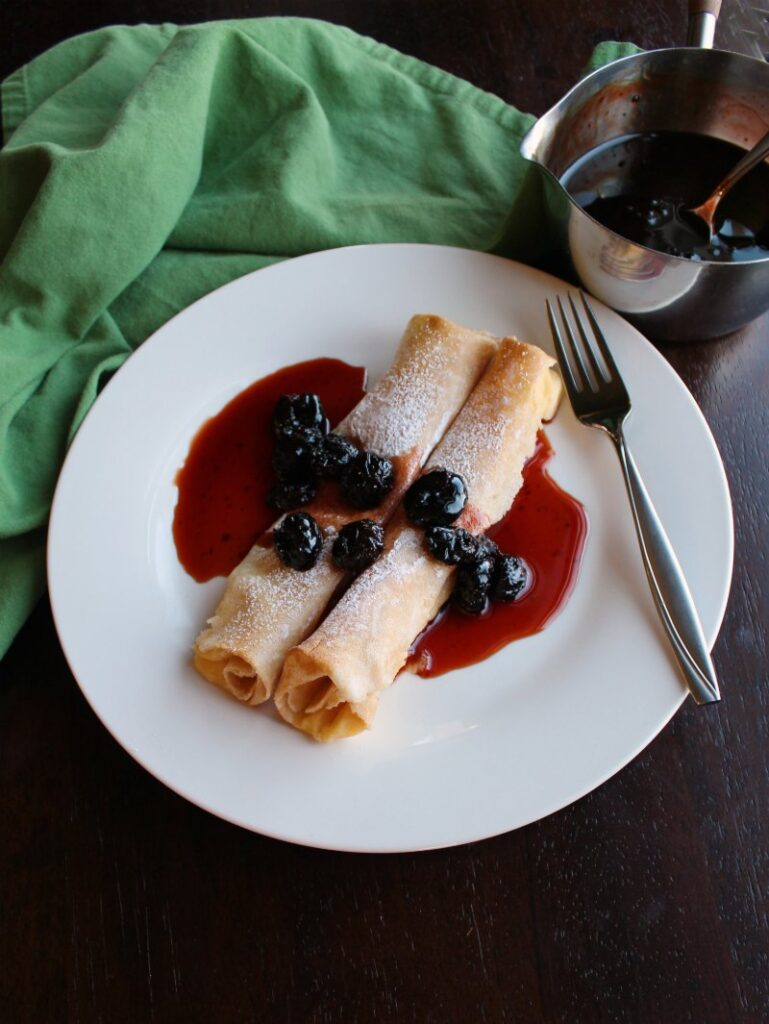 lemon ricotta stuffed crepes on plate with cherry syrup.